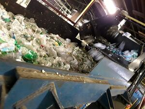 PET bottles on conveyer belt at PQ Recycling plant; soon they will converted to flake for reuse to make new bottles, packaging, and other PET products like strapping tape.