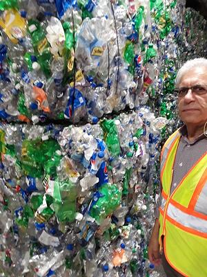 George Smilow, COO of Polyquest Recycling, stands by stack of PET bales from redemption centers at PQ's plant on Long Island.